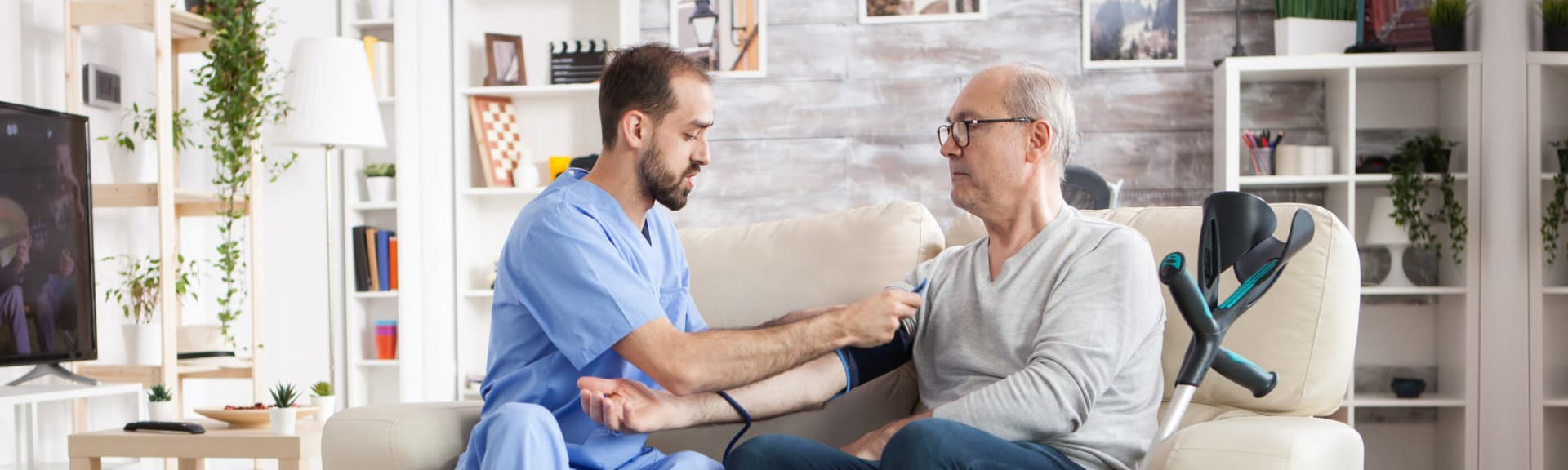 caregiver checking blood pressure of senior man